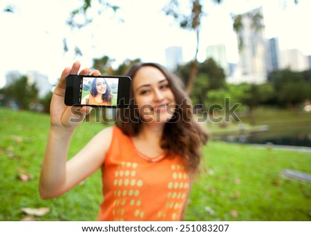 girl sitting in the park of Kuala Lumpur on the background of business centers and makes selfie, happy