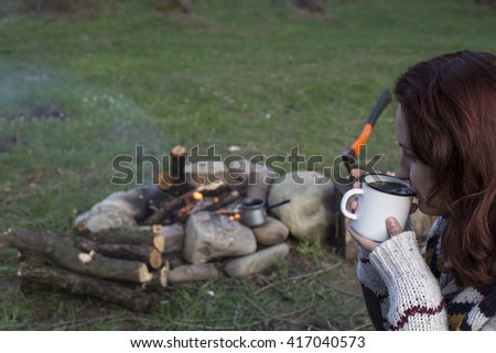 Girl sitting near a campfire at the campsite looking at map and drinking coffee. - stock photo