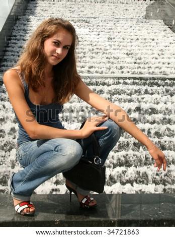 Girl sitting near fountain - stock photo