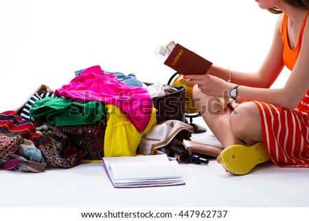 Girl sitting near overfilled suitcase. Woman holding passport with banknote. Getting ready for travelling. Long way from home. - stock photo