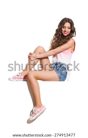 Girl Sitting on a Banner. Smiling sexy woman in pink top, jeans shorts and pink sneakers sitting on the white banner and looking down. Full length studio shot isolated on white. - stock photo