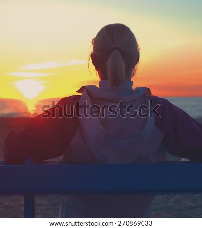 Girl sitting on a beach and looking on sinset  - stock photo
