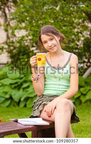 Girl sitting on a bench in the garden and holding a cup - stock photo