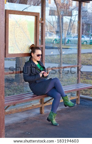 Girl sitting on a bench waiting for transport at the bus stop. Waiting for transport studies mobile phone - stock photo