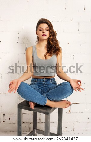 Girl sitting on a chair in yoga pose. White brick wall not isolated - stock photo