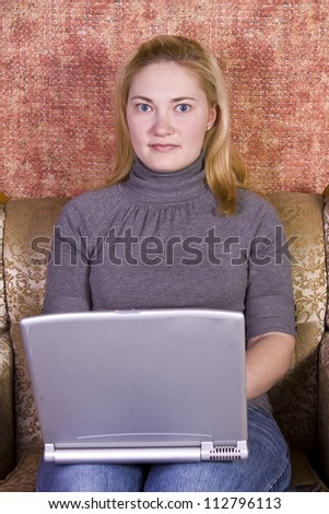 Girl sitting on a chair working on her Laptop - stock photo