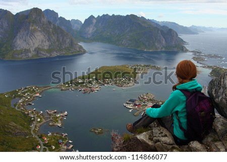 girl sitting on a cliff and looking at the Reine - stock photo