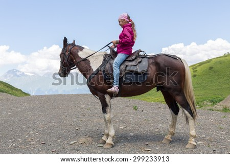 girl sitting on a horse in the mountains - stock photo