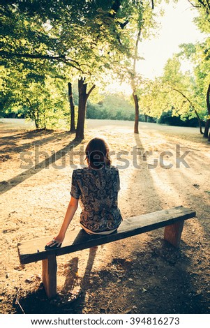 Girl sitting on a park bench facing the sun. From the back - stock photo