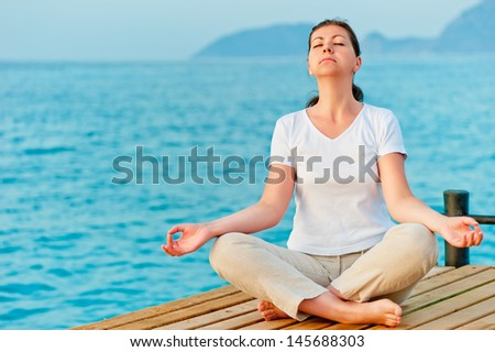 girl sitting on a pier in the lotus position - stock photo