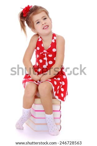 Girl sitting on a pile of books.Isolated on white background - stock photo