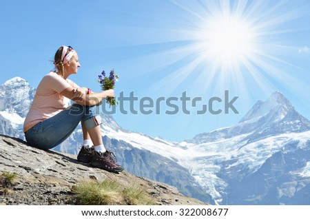 Girl sitting on a rock against Swiss Alps - stock photo