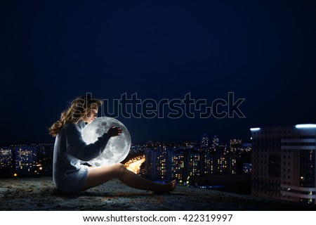 girl sitting on a roof at night, hugging the moon. Against the background is seen the city night, he believes in a fairy tale, waiting for a miracle. The free part of a sign, banner poster. - stock photo