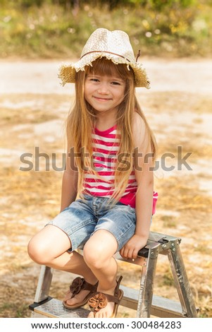 Girl sitting on a stepladder outdoor. Summer time.  - stock photo