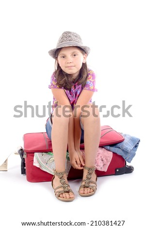 girl sitting on a suitcase on the white background - stock photo
