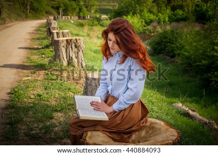 girl sitting on a tree stump in Alley of felled trees is reading a book - stock photo