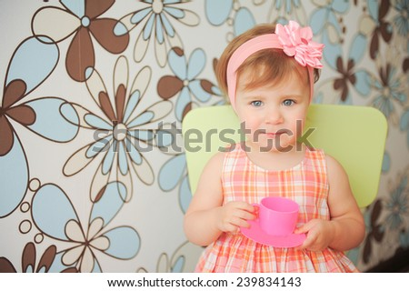 girl sitting on chair and holding pink cup and saucer - stock photo