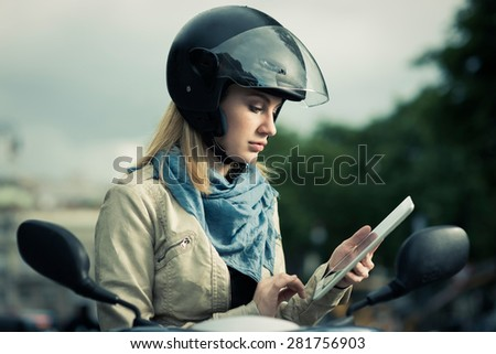 Girl sitting on her scooter with digital tablet, looking direction on GPS - stock photo