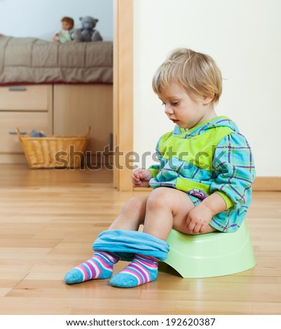 girl sitting on potty in home  - stock photo