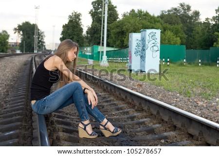 Girl sitting on rails - stock photo