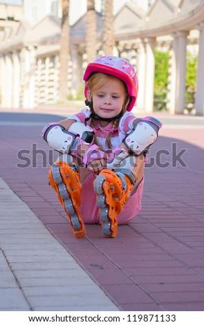 Girl sitting on roller skates - stock photo