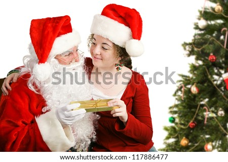 Girl sitting on Santa Claus' lap, getting a Christmas present from him.  Isolated on white. - stock photo
