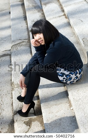 Girl sitting on stairs - stock photo
