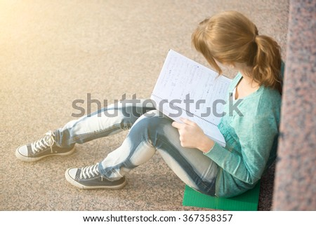 Girl sitting on stairs and reading note - stock photo
