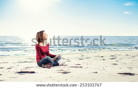 Girl sitting on the beach with a computer - stock photo