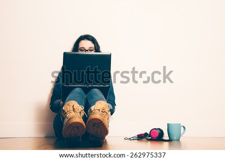 Girl sitting on the floor with a laptop looking at screen concentrated. Filter effect added. - stock photo