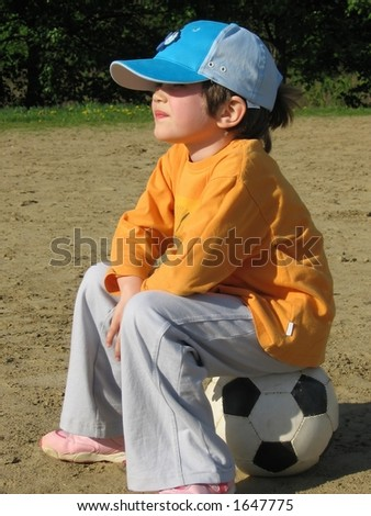 girl sitting on the football;  she like this game - stock photo