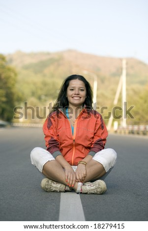 Girl sitting on the road in mountain - stock photo