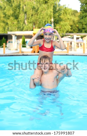 Girl sitting on the shoulders of her brother and wears goggles in the outdoor swimming pool - stock photo