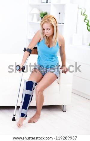 Girl sitting on the sofa having leg injury - stock photo