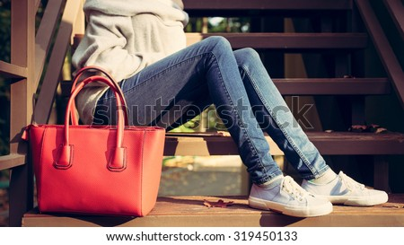Girl sitting on the stairs with a big red super fashionable handbags in a sweater jeans and sneakers on a warm summer evening. Warm colors - stock photo