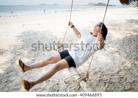 Girl sitting on the swing on the tropical beach, paradise island. - stock photo