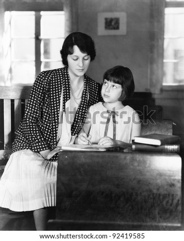 Girl sitting with her teacher in a class room - stock photo