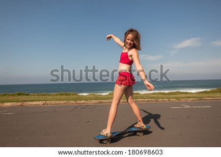 Girl Skateboarding Holidays Young girl skateboarding on beach road family holiday - stock photo