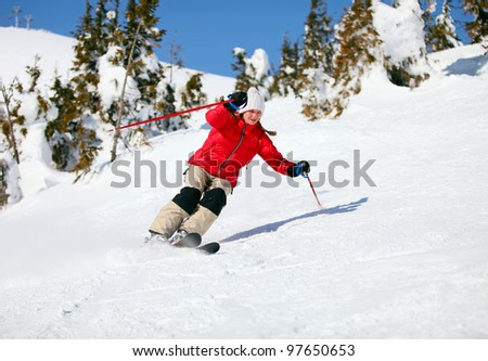 Girl skier moving down the slope - stock photo