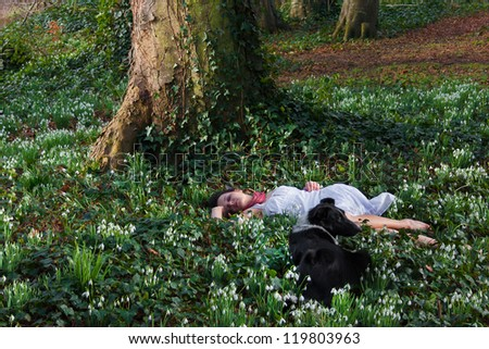Girl sleeping between snowdrops and her dog is watching over her - stock photo