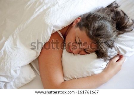 girl sleeping on his stomach hugging pillow - stock photo