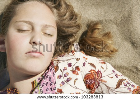 Girl sleeping while laying down on a golden sand beach on a sunny day. - stock photo