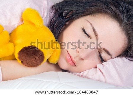 girl sleeping with teddy bear in bed - stock photo