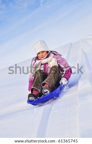 Girl slides down a hill on a sledge on a background of blue sky - stock photo
