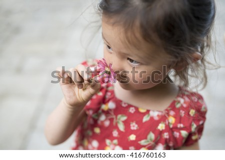 Girl smell the fragrance of flower - stock photo
