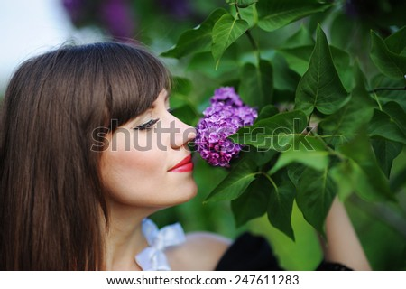 girl smelling a purple lilacs in the spring in the park. - stock photo
