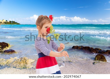 girl smelling a rose on the beach.floral bouquet, flowers delight,happiness concept,happy childhood,carefree childhood,active lifestyle - stock photo