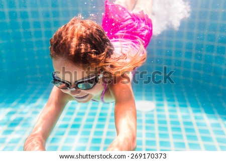 Girl smiles, swimming under water in the pool - stock photo