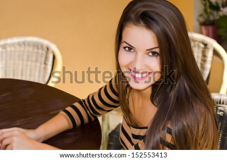 Girl smiling at a cafe bar. Beautiful woman sitting alone at a table, waiting to be served. - stock photo