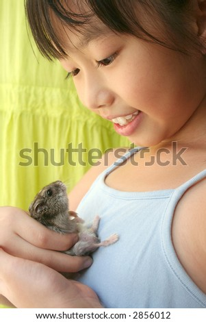Girl smiling happily and playing with her grey pet hamster - stock photo